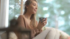 A mulher feliz nova aprecia do copo do café quente que senta-se em casa pela janela grande com fundo da árvore da neve do inverno video estoque