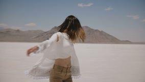 Mulher feliz nova bonita que anda e que gerencie no lago quente ensolarado do deserto de sal de Bonneville que veste a roupa ocas filme