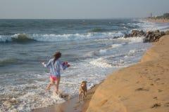 Mulher feliz nova bonita que corre junto com seu cão n a praia imagens de stock royalty free
