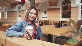 Mulher feliz nova bonita que senta-se no café e que fala no telefone vídeos de arquivo