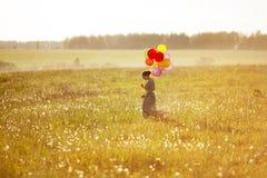 Mulher feliz nova com balões em um campo imagem de stock royalty free