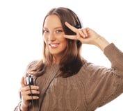 Mulher feliz nova com música de escuta dos fones de ouvido Fotografia de Stock