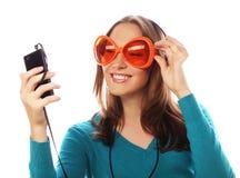 Mulher feliz nova com música de escuta dos fones de ouvido Imagem de Stock Royalty Free