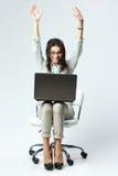 Mulher feliz nova com os braços que sentam-se acima na cadeira com portátil Foto de Stock Royalty Free