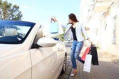 Mulher feliz nova com os sacos de compras perto do carro fora Fotos de Stock