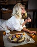 A mulher feliz nova come panquecas frescas no café da manhã na cozinha moderna em casa foto de stock
