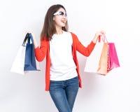 Mulher feliz nova da compra do verão com os sacos de compras isolados no fundo cinzento, retrato da mulher de sorriso feliz nova  foto de stock