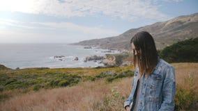 A mulher feliz nova de sorriso atrativa olha a câmera na costa épico do oceano do Big Sur coberta com as flores amarelas luxúrias vídeos de arquivo