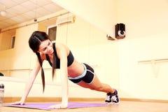 Mulher feliz nova do ajuste que faz flexões de braço Foto de Stock