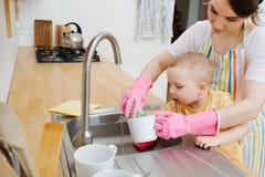 A mulher feliz nova em uma cozinha está lavando copos e pratos Suas ajudas pequenas do filho imagens de stock