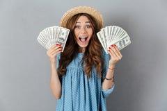 Mulher feliz nova entusiasmado que guarda o dinheiro olhando a câmera foto de stock