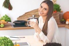 A mulher feliz nova está guardando o copo branco e está olhando a câmera ao sentar-se na tabela de madeira na cozinha entre Imagens de Stock Royalty Free