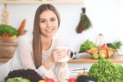 A mulher feliz nova está guardando o copo branco e está olhando a câmera ao sentar-se na tabela de madeira na cozinha entre Fotos de Stock