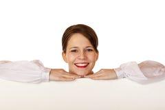 A mulher feliz nova inclina-se no quadro de avisos em branco fotos de stock
