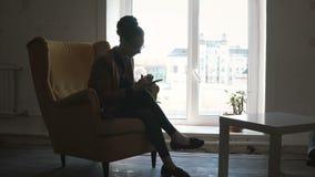 Mulher feliz nova na cadeira amarela e em guardar o smartphone Fêmea que usa o telefone celular para o trabalho vídeos de arquivo