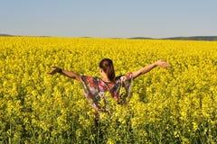 A mulher feliz nova no campo de florescência da colza na mola Fotografia de Stock