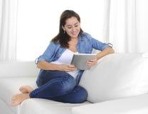 Mulher feliz nova no sofá em casa que aprecia usando o tablet pc digital imagens de stock