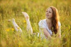 A mulher feliz nova olha fora da grama Imagens de Stock