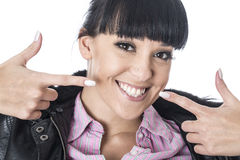 Mulher feliz nova que aponta ambos os dedos em seu sorriso bonito Fotografia de Stock