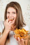 Mulher feliz nova que come microplaquetas Fotos de Stock Royalty Free