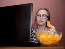 Mulher feliz nova que come microplaquetas perto de um computador Conceito insalubre foto de stock