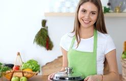 Mulher feliz nova que cozinha a sopa na cozinha Refeição saudável, estilo de vida e conceito culinário Menina de sorriso do estud foto de stock royalty free