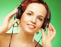 Mulher feliz nova que escuta a música com fones de ouvido fotos de stock royalty free