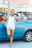 Mulher feliz nova que está perto de um convertible com as chaves em h Fotos de Stock Royalty Free