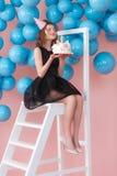 Mulher feliz nova que guarda o bolo do unicórnio, fazendo o desejo com olhos fechados Conceito do aniversário Foto de Stock Royalty Free