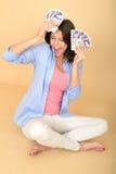 Mulher feliz nova que guarda o dinheiro que olha satisfeito e deleitado Foto de Stock