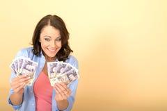 Mulher feliz nova que guarda o dinheiro que olha satisfeito e deleitado Imagem de Stock