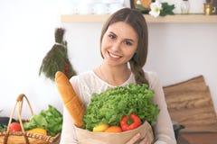 Mulher feliz nova que mantém o saco de papel completo dos vegetais e dos frutos ao sorrir A menina fez a compra e apronta-se para Fotos de Stock Royalty Free