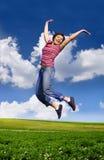 Mulher feliz nova que salta altamente de encontro ao céu azul fotos de stock