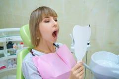 Mulher feliz nova que senta-se no escritório do dentista, dentes saudáveis imagens de stock