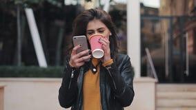 Mulher feliz nova que usa o smartphone e bebendo o café para ir fora, andando abaixo da rua da cidade, movimento lento filme
