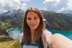 A mulher feliz nova toma um selfie na parte superior da montanha nos cumes suíços fotografia de stock royalty free