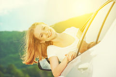 A mulher feliz olha para fora a janela de carro na natureza Fotos de Stock