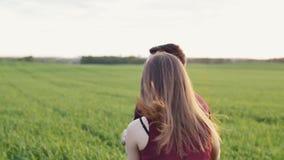 A mulher feliz persegue seu homem que corre no campo no por do sol Salta na sua para trás Backview, mo lento, tiro do steadicam vídeos de arquivo