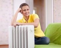 Mulher feliz perto do calefator imagem de stock