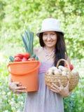 A mulher feliz prende a colheita dos vegetais Imagens de Stock