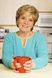 A mulher feliz prende uma caneca de café em sua cozinha Imagem de Stock Royalty Free