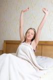 Mulher feliz que acorda e que estica seus braços acima Fotos de Stock Royalty Free