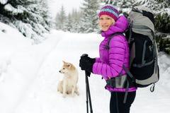 Mulher feliz que anda na floresta do inverno com cão Imagem de Stock