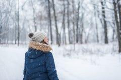 mulher feliz que anda nas madeiras do inverno que olham acima na queda da neve imagem de stock