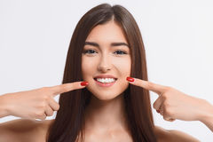 Mulher feliz que aponta o dedo em seu sorriso toothy Imagem de Stock Royalty Free