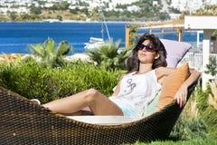 A mulher feliz que aprecia as férias de verão que colocam sobre sunbed em um jardim tropical Fotos de Stock