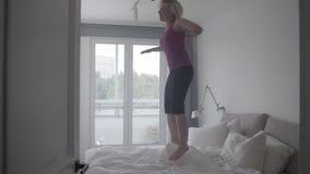 Mulher feliz que aprecia seu apartamento, saltando na cama em casa, zorra do movimento lento dentro vídeos de arquivo