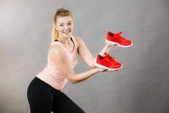 Mulher feliz que apresenta a instrutores do sportswear sapatas imagem de stock