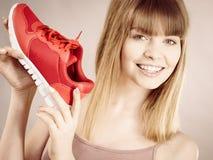 Mulher feliz que apresenta a instrutores do sportswear sapatas foto de stock