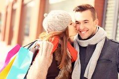 Mulher feliz que beija um homem ao comprar foto de stock royalty free